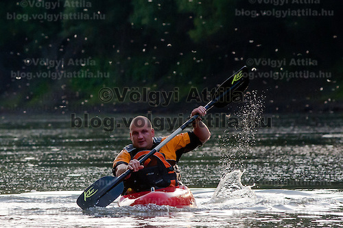 Local man paddles a kayak during the few days long swarming of the long-tailed mayfliy (Palingenia longicauda) on the river Tisza in Tiszainoka (some 135 km south-east from Budapest), Hungary on June 12, 2011. ATTILA VOLGYI