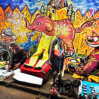 A Colombian man sells vintage items in front the wall, covered in a graffiti artwork, during the flea market in the center of Bogotá, Colombia, 21 February, 2016. A social environment full of violence and inequality (making the street art an authentic form of expression), with a surprisingly liberal approach to the street art from Bogotá authorities, have given a rise to one of the most exciting and unique urban art scenes in the world. While it's technically not illegal to scrawl on Bogotá's walls, artists may take their time and paint in broad daylight, covering the walls of Bogotá not only in territory tags and primitive scrawls but in large, elaborate artworks with strong artistic style and concept. Bogotá has become an open-air gallery of contemporary street art.