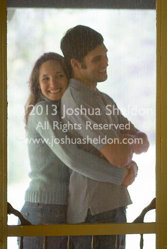 Man & woman embracing outside screen door