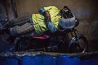 un conduttore di moto taxi dorme sulla sua motocicletta