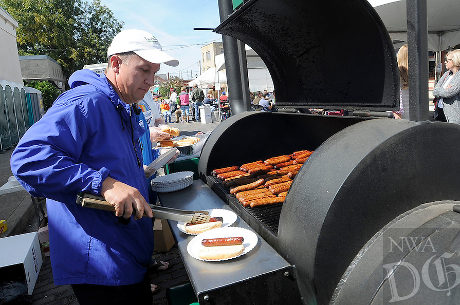 STAFF PHOTO FLIP PUTTHOFF <br /> Russell Ellis grills bratwurst on Saturday Oct. 4 2014 during the Oktoberfest and Craft Beer Experience in downtown Rogers. The event featured music, a variety of craft beers and bratwurst meals.