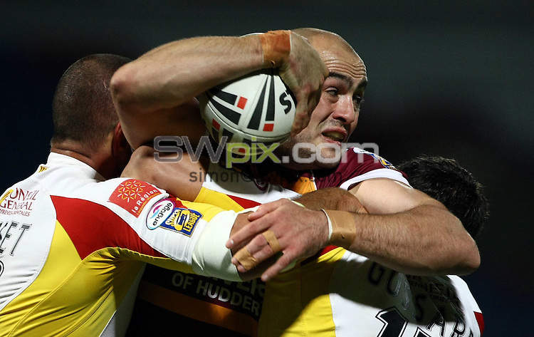 PICTURE BY VAUGHN RIDLEY/SWPIX.COM - Rugby League - Super League Playoffs - Huddersfield v Catalans - Galpharm Stadium, Huddersfield, England  - 25/09/09...Copyright - Simon Wilkinson - 07811267706...Huddersfield's Andy Raleigh is tackled by Catalans Jerome Guisset and Cyrille Gossard.