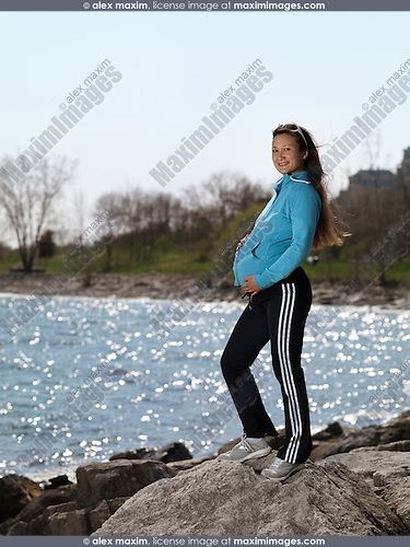 Pregnant young woman standing on a rocky shore near water