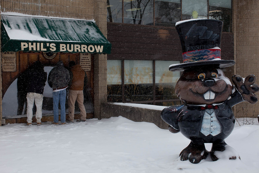 Visitors look for Punxsutawney Phil inside of his burrow at the library in Punxsutawney, PA
