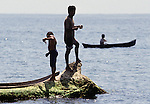 Two boys fish from a log while another fishes from his canoe. the island republic of Palau has been everything from a Japanese military base to a U.S. Trust territory it now seeks profitable indignity as a plush Pacific resort..The Republic of Belau lies 1,300 kilometers, southwest of Guam, and 600 kilometers east of the Philippines. (Jim Bryant Photo).....