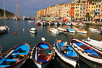 Colorful boats sit moored at a dock in the Ligurian town of Porto Venere, the gateway to Italy's Cinque Terre region.