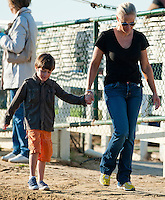 Bode Baffert walks with him mother Jill from morning workouts on Black-Eyed Susan Day at Pimlico Race Course in Baltimore, Maryland on May 18, 2012.
