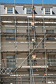 Construction workers erecting scaffolding on an apartment block, Richmond, London.