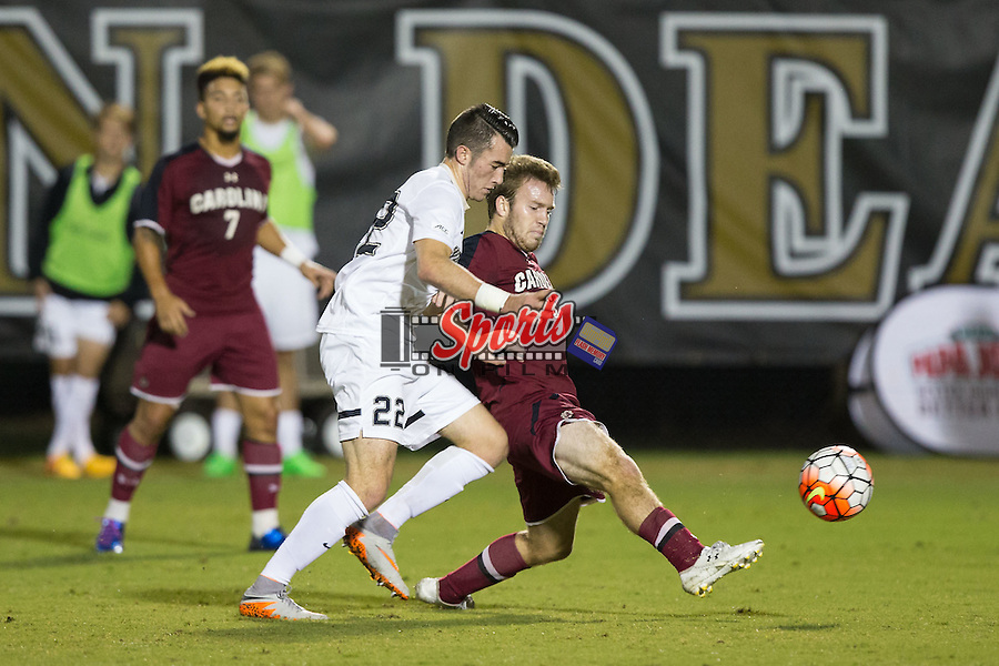 Koty Millard (5) of the South Carolina Gamecocks passes the ball away from Jack Harrison (22) of the Wake Forest Demon Deacons during first half action at Spry Soccer Stadium on October 6, 2015 in Winston-Salem, North Carolina.  The Demon Deacons defeated the Gamecocks 2-0.  (Brian Westerholt/Sports On Film)