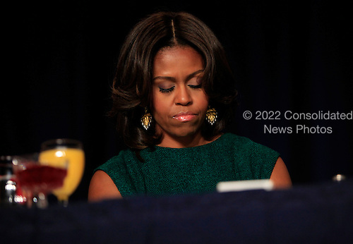 First lady Michelle Obama bows her head in prayer as she and United States President Barack Obama attend the National Prayer Breakfast at the Washington Hilton Hotel in Washington, D.C. on February 5, 2015.  U.S. and international leaders from different parties and religions gather annually at this event for an hour devoted to faith and prayer.<br /> Credit: Dennis Brack / Pool via CNP