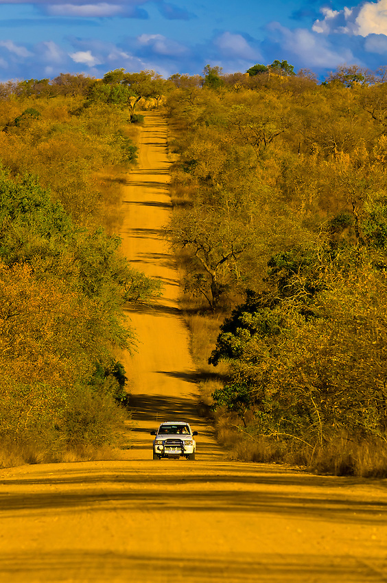 Safari vehicle driving down a long road in Kruger National Park, South Africa