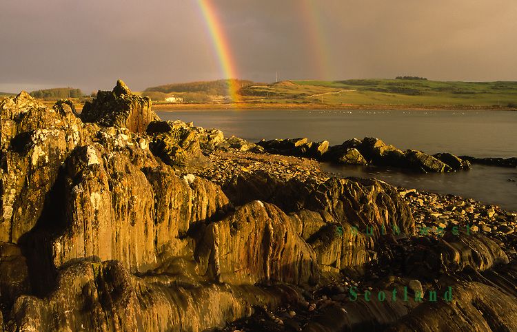 Looking across Brighouse Bay on the Solway Firth coast to dark rain clouds and rainbow Galloway Scotland UK
