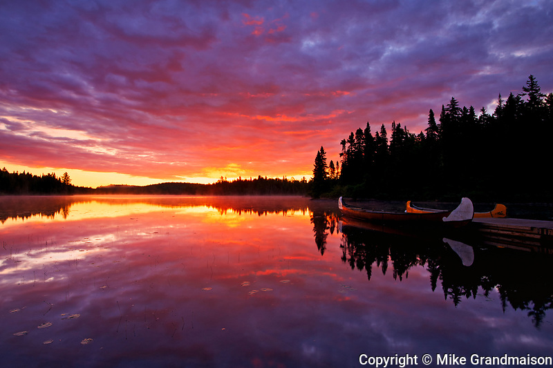 Reflection of clouds in Lac du Fou at sunrise with canoes<br />La Mauricie National Park<br />Quebec<br />Canada<br />La Mauricie National Park<br />Quebec<br />Canada