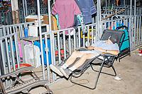 A person sleeps near animal pens in the Sheep Barn at the Iowa State Fair in Des, Moines, Iowa, on Sun., Aug. 11, 2019.