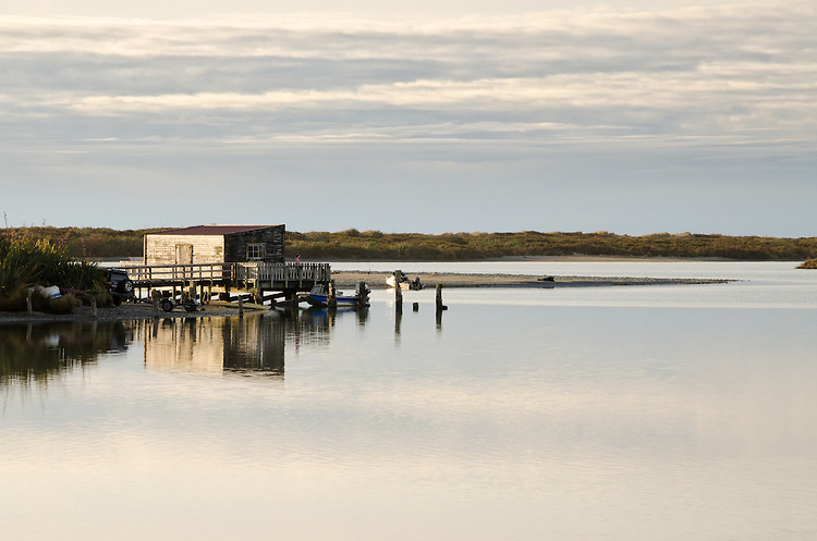Old shed reflected in Okarito Lagoon, South Westland, New Zealand - stock photo, canvas, fine art print