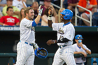 UCLA second baseman Cody Regis (18) greets teammate  Brenton Allen (23) after he scored against the Mississippi State Bulldogs during the 2013 Men's College World Series Final on June 25, 2013 at TD Ameritrade Park in Omaha, Nebraska. The Bruins defeated the Bulldogs 8-0, winning the National Championship. (Andrew Woolley/Four Seam Images)