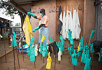 Health care worker Tamba K. Kamano hangs freshly bleached reusable PPE items at the ELWA II ETU (Ebola treatment unit) in Monrovia, Liberia on Tuesday, March 3, 2015. The ETU, operated by ELWA Hospital, was the first to open in Monrovia.<br /> (Photo by Marc Campos, Occidental College Photographer) Mary Beth Heffernan, professor of art and art history at Occidental College, works in Monrovia the capital of Liberia, Africa in 2015. Professor Heffernan was there to work on her PPE (personal protective equipment) Portrait Project, which helps health care workers and patients fighting the Ebola virus disease in West Africa.<br />