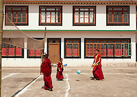 A moment in the day of student Buddhist monks at a monastery in the Himalayan foothills of Sikkim, India. Playing soccer in the sun, in their robes.