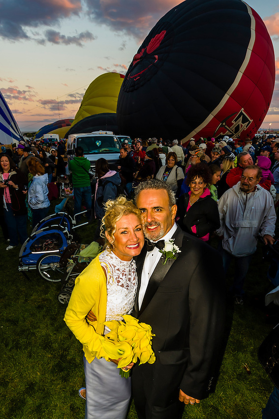 A just married couple pose before lifting off in a hot air balloon at the Albuquerque International Balloon Fiesta, Albuquerque, New Mexico USA.