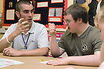 Boy with learning disability and teacher sitting at desk in classroom working on maths problem. MR