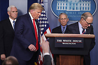 Director of the National Economic Council Larry Kudlow, right, leaves the podium as United States President Donald J. Trump, left center, returns to speak during a press conference with members of the coronavirus task force in the Brady Press Briefing Room of the White House on March 24, 2020 in Washington, DC.  At left is US Vice President Mike Pence and at right center is Director of the National Institute of Allergy and Infectious Diseases at the National Institutes of Health Dr. Anthony Fauci.<br /> Credit: Oliver Contreras / Pool via CNP/AdMedia