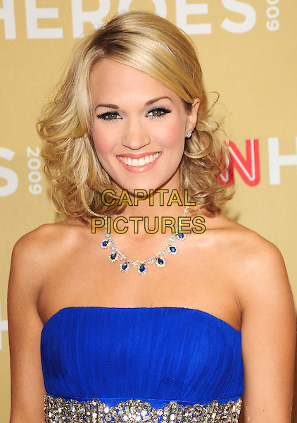 CARRIE UNDERWOOD .at The 3rd Annual CNN Heroes: An All-Star Tribute held at The Kodak Theatre in Hollywood, California, USA,  November 21st 2009                                                                   .portrait headshot strapless blue necklace smiling sapphire and diamond .CAP/RKE/DVS.©DVS/RockinExposures/Capital Pictures