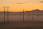 Sunrise with power lines and telephone wires stretching across valley floor