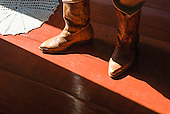 Cowboy boots, red floor, white crochet mat, sunshine.