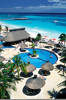 Mexico, Playa del Carmen. Beach resort with pool and palapas at waters edge