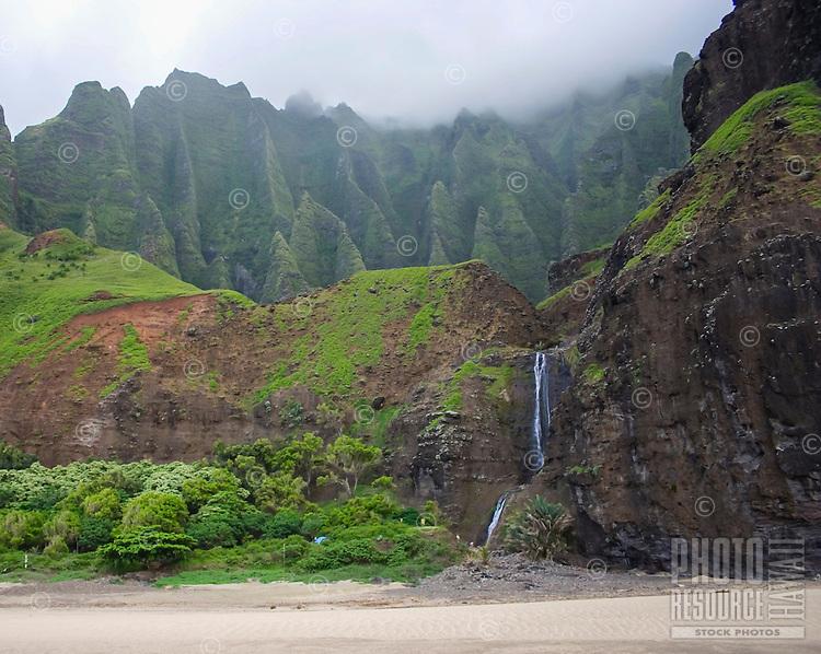 The waterfall at Kalalau Beach, with mountains in the distance, Na Pali Coast, Kaua'i.
