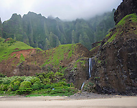 The waterfall at Kalalau Beach, with mountains in the distance, Na Pali Coast, Kaua'i.