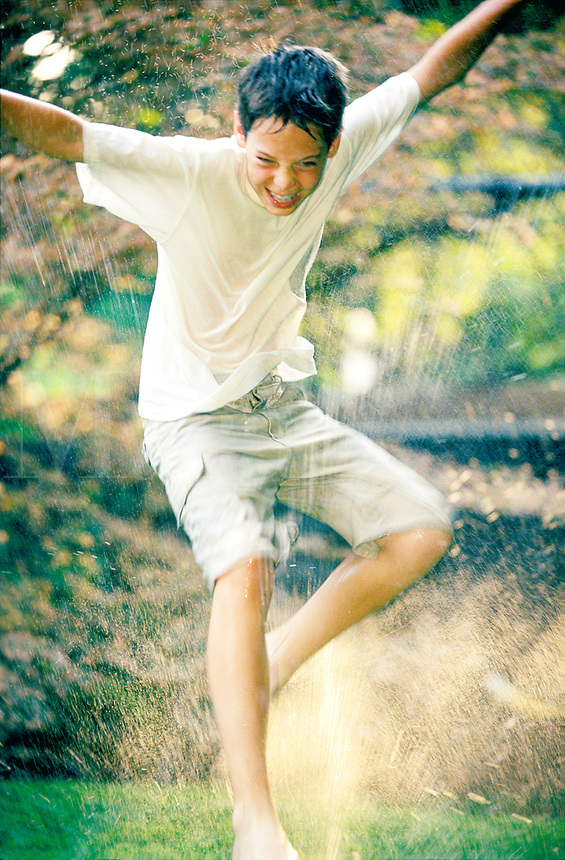 Teen boy playing in the summertime sprinklers