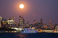 A full moon rises over the skyline of New York , April 25, 2013. by Kena Betancur / VIEWpress
