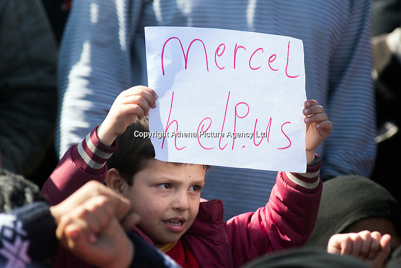"""Pictured: A little boy with a """"Merkel help us"""" slogan on a piece of paper Thursday 03 March 2016<br /> Re: Migrants have closed off the railway track at the Greek Fyro Macedonian border in Idomeni, Greece,"""