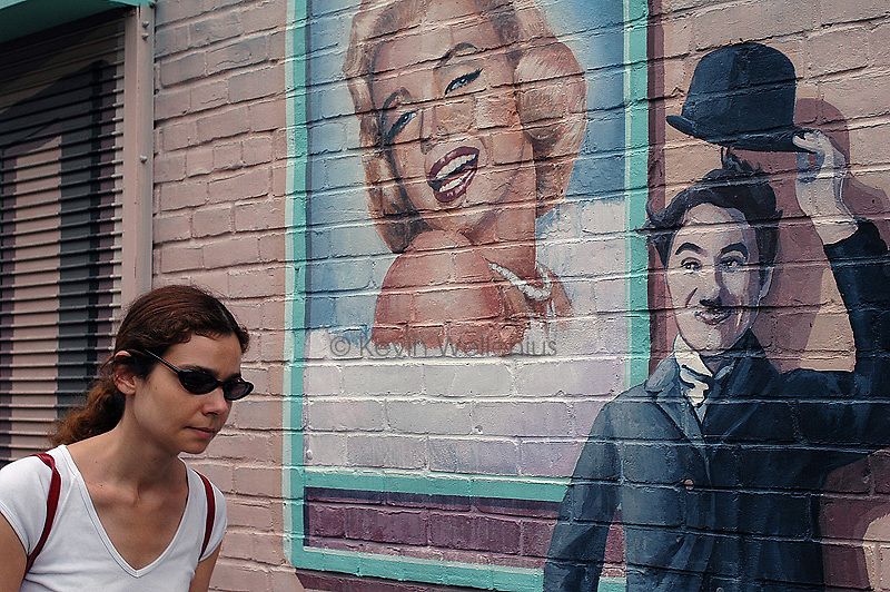 A pedestrian is greeted by a mural of movie icons, including Marilyn Monroe and Charlie Chaplin, in front of the Harvard Square Theatre in Cambridge, Mass.