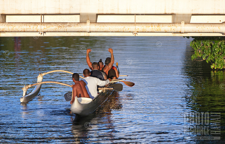 Local men paddling a canoe on Anahulu River under the bridge in Haleiwa, O'ahu.
