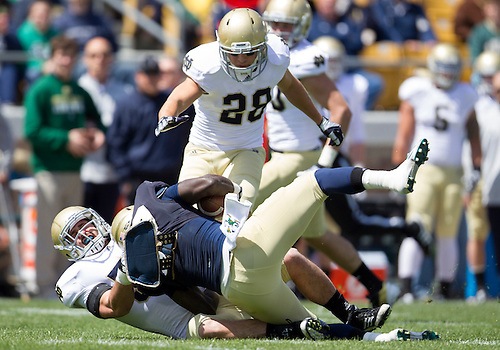 April 21, 2012:  Notre Dame Fighting Irish running back Cierre Wood (20) is tackled after a short gain in first quarter action of the Notre Dame Blue-Gold Spring game at Notre Dame Stadium in South Bend, Indiana.  The Defense topped the Offense by a score of 42-31.