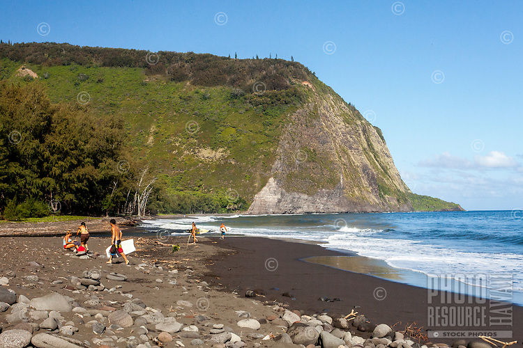 Kids with surfboards and bodyboards walking on the black sand beach in Waipi'o Valley, Big Island.