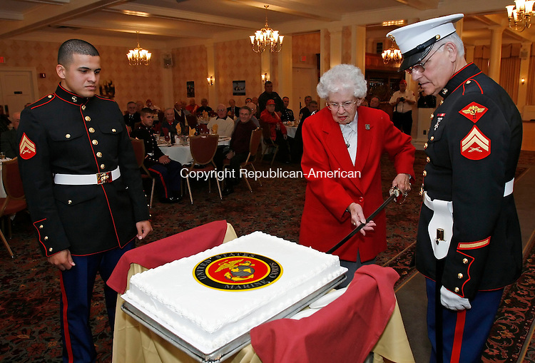 TORRINGTON, CT, 11/09/08- 110908BZ03- U.S. Marine Corps Cpl. Jean Ramos, of the Inspector and Instructor Company in Plainville, left, the youngest Marine in attendence, watches as the oldest Marine, Edna Juan-Wells, of Torrington, who served in the Corps from 1944 thorugh 1946 as a motor transport and auto mechanic, cuts a ceremonial cake celebrating the 233rd birthday of the Corps at the Elks Lodge in Torrington Monday night.  At right is George Budzyn, co-chair of the birthday committee and Vietnam era Marine Cpl.<br /> Jamison C. Bazinet Republican-American