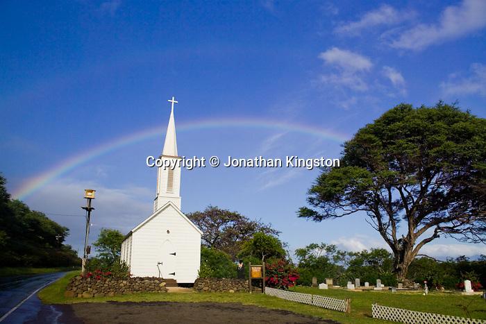 MOLOKAI, HI - Tsunami warning system siren, next to Saint Damien's church, cemetery and rainbow on the Pacific island of Molokai, Hawaii.