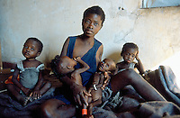 Angola. Cuando Cubango. Mavinga. Mother breastfeeding her twin sisters, both malnourished children,. She is seated on a bed in a hospital run by MSF (M?decins Sans Frontires) Switzerland. The twin brothers are also her children, they sit each on her side. One of her daughter will die a few days later. © 2002 Didier Ruef