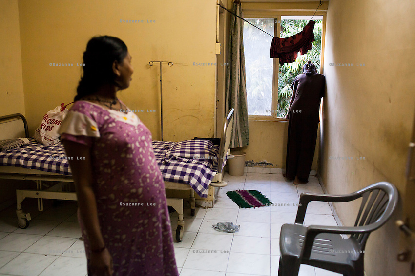 Surrogates pass their time watching the happenings outside through their windows in the surrogates hostel on the 3rd floor of Dr. Nayana Patel's Akanksha IVF and surrogacy center in Anand, Gujarat, India on 10th December 2012. Photo by Suzanne Lee / Marie-Claire France