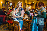 A mother breastfeeds her two year old daughter in the family restaurant and play area of a pub. The mother is standing and the boy is feeding while standing on a chair.<br /> <br /> Lancashire, England, UK<br /> <br /> Date Taken:<br /> 07-01-2015<br /> <br /> &copy; Paul Carter / wdiip.co.uk