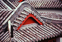 Fine art travel detail of Beijing roof tile patterns, showing inverted, curved red arch under greyish arching roof structure of tiles, with tiles from the next structure in the background, Beijing, China.
