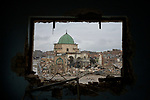 The ruins of the Great Mosque of al-Nuri on November 30, 2018, in the Old City of Mosul, Iraq, seen through the window of a war-damaged house nearby. Built over 800 years ago, the mosque was blown up by ISIS combatants during the final moments of the 2017 Battle of Mosul.