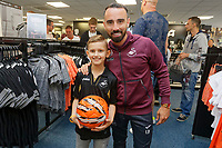 Pictured: Leon Britton with a young fan. Friday 24 August 2018<br /> Re: Swansea City FC third kit launch at the club shop, Liberty Stadium, Swansea, Wales, UK.