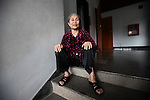 An elderly woman sits at the top of a staircase inside the Reunification Palace in Ho Chi Minh City, Vietnam.  June 30, 2011.