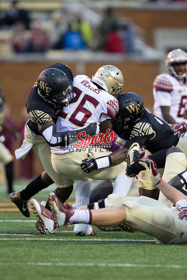 Johnathan Vickers (26) of the Florida State Seminoles is tackled by Marquel Lee (8) and Cameron Glenn (2) of the Wake Forest Demon Deacons during second half action at BB&T Field on October 3, 2015 in Winston-Salem, North Carolina.  The Seminoles defeated the Demon Deacons 24-16.   (Brian Westerholt/Sports On Film)