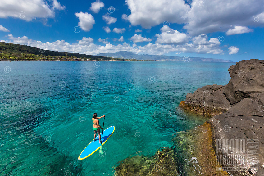 A woman standup paddles along a rocky shoreline in the calm waters of Waimea Bay, North Shore, O'ahu.