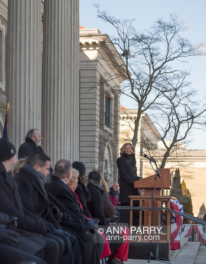 Mineola, New York, USA. January 1, 2018. Historic swearing-In of LAURA CURRAN as Nassau County Executive, the first female County Executive, is held outdoors. Temperature was a freezing 14 ℉ Fahrenheit / -10 ℃  Celsius for the outdoor ceremony held in front of Theodore Roosevelt Executive & Legislative Building, and people in audience stood close together on and near the vast entrance stairs steps. Welcome was by Mayor FRANCIS MURRAY of Rockville Centre.